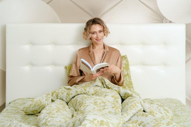 Clever jeune femme est assise dans son lit sous la couverture avec un livre en mains