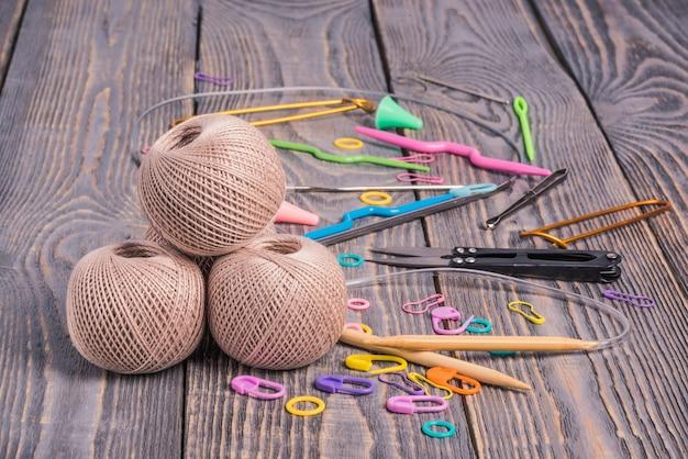 Clews de fil, des aiguilles à tricoter, des ciseaux et des clips sur fond en bois.