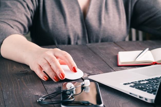 Clic de souris, main de femme avec souris et ordinateur portable