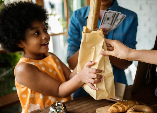 Client achetant du pain frais au four dans une boulangerie
