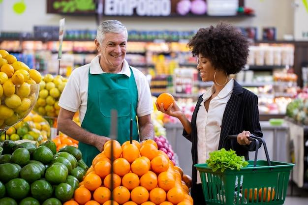 Client africain avec marchand de légumes, tenant des fruits orange.