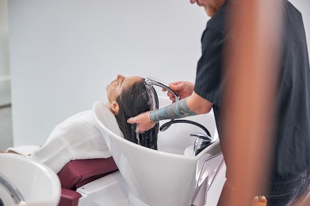 Client appréciant les soins capillaires dans le salon de coiffure
