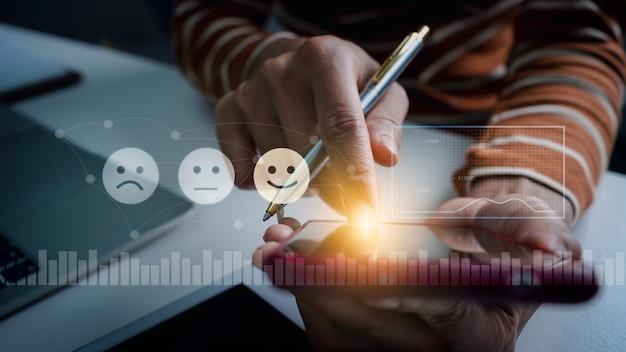 Client appuyant sur l'émoticône du visage de l'écran mobile sur l'écran vr, évaluation de la satisfaction du client avec l'utilisation d'écrans virtuels.