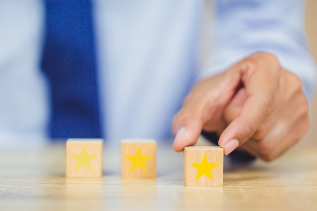 Client appuyant sur l'étoile sur cube de bois, cote de service, concept de satisfaction.