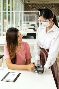 Un client asiatique effectue un paiement par carte de crédit sans contact