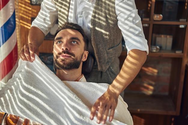Un client de barbier aux yeux bleus se penchant en arrière dans un fauteuil avec une serviette sur la poitrine