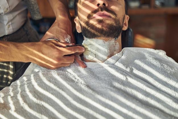 Un client de barbier couvert de crème à raser ayant la main d'un barbier près de sa gorge