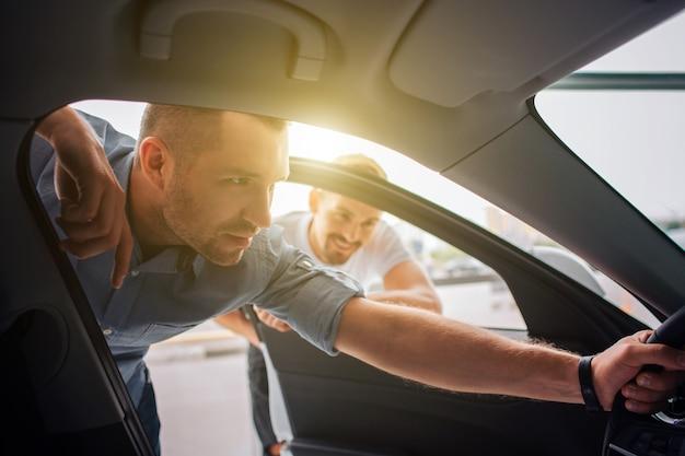 Un client beau et confiant se tient debout et se penche sur la voiture