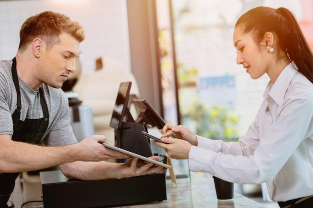Client de café utilisant les services bancaires sur internet mobiles scannant le code de paiement qr pour une boisson au café du personnel du barista au comptoir, concept de mode de vie moderne de la société sans numéraire