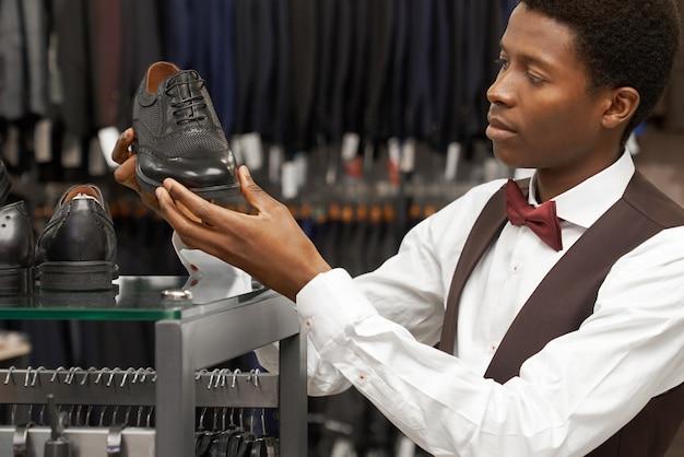 Client choisissant des chaussures élégantes en boutique.