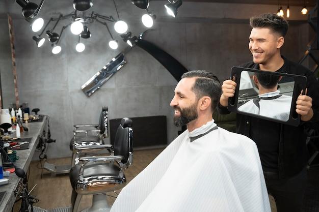 Client et coiffeur heureux de coup moyen