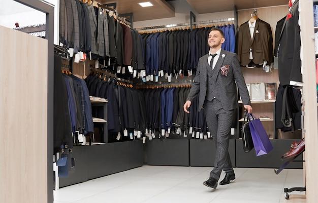Client en costume dans une boutique avec des sacs à provisions.
