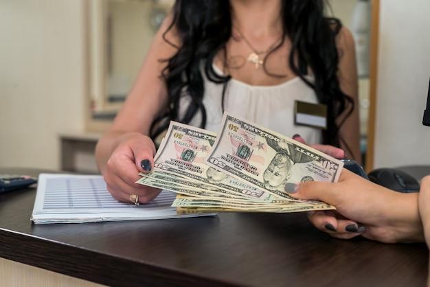 Le client dans le salon de beauté donne des dollars à la réceptionniste