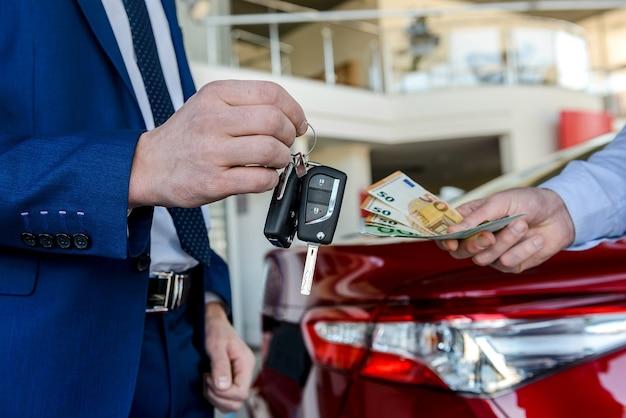Client donnant l'euro au concessionnaire et concessionnaire donnant les clés