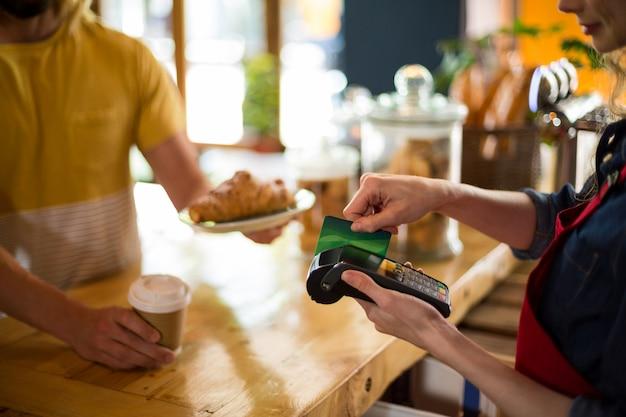 Client effectuant le paiement par carte de crédit au comptoir en café