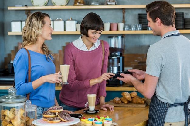 Client effectuant le paiement via le terminal de paiement au comptoir