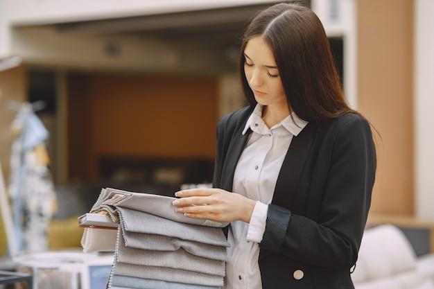 Client de femme à la recherche de beau tissu dans une boutique de draperie