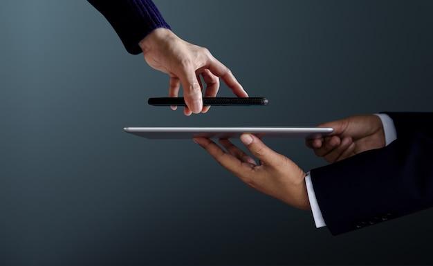 Client de femme utilisant smartphone pour effectuer la transaction de paiement avec un homme d'affaires