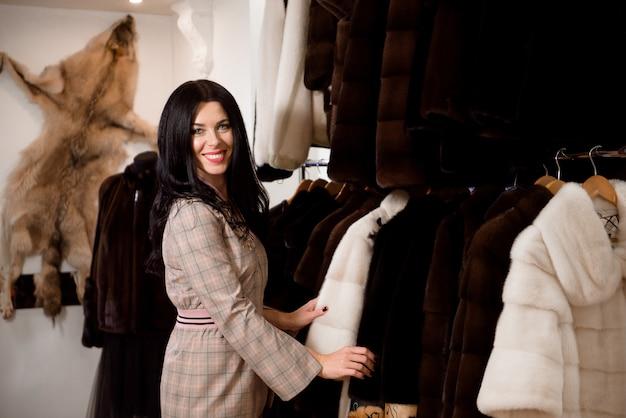 Client fille examinant le nouveau manteau de fourrure dans le magasin de vêtements pour femmes