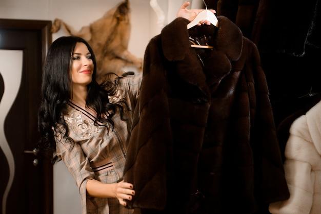Client fille examinant un nouveau manteau de fourrure dans le magasin de vêtements pour femmes