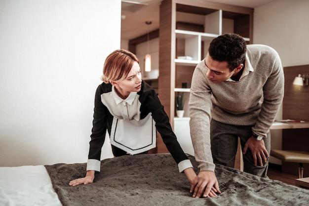 Client flirtant. blonde jeune belle femme de ménage se sentant effrayée pendant que le client flirte avec elle