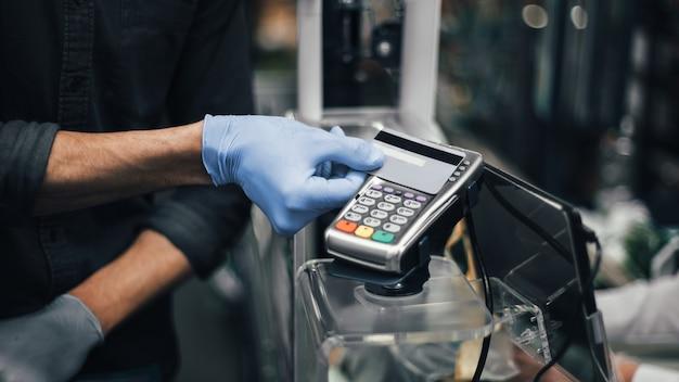 Client en gants de protection payant des marchandises dans un supermarché. hygiène et soins