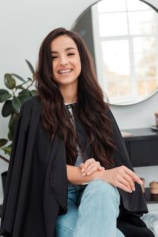 Client heureux assis sur une chaise et souriant