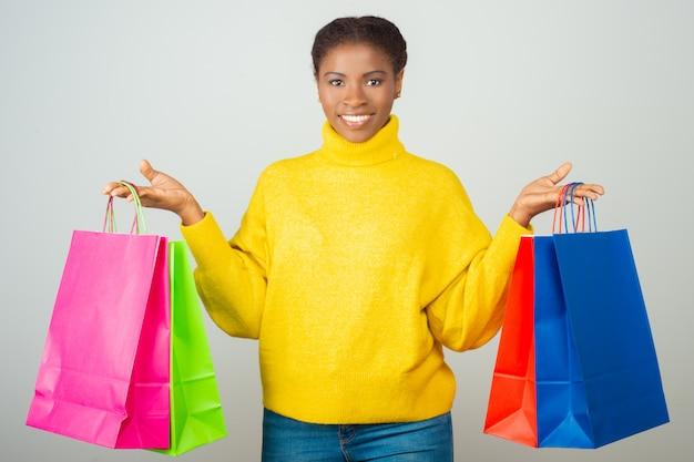 Client heureux tenant et montrant des sacs à provisions colorés