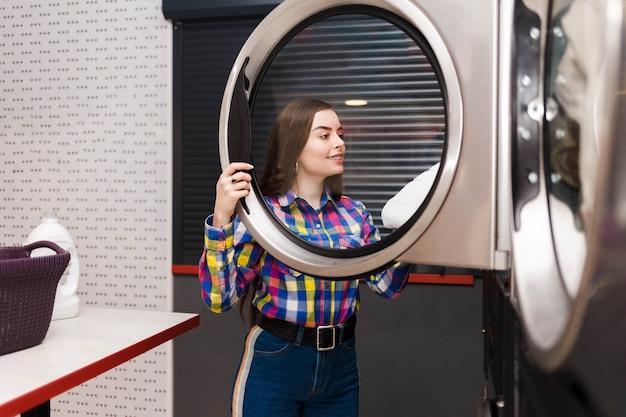 Client de laverie libre-service prend les choses hors de la sécheuse