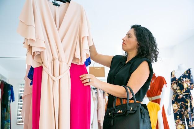 Client de magasin de mode ciblé choisissant des vêtements et parcourant des robes sur un support. plan moyen, vue latérale. magasin de mode ou concept de vente au détail