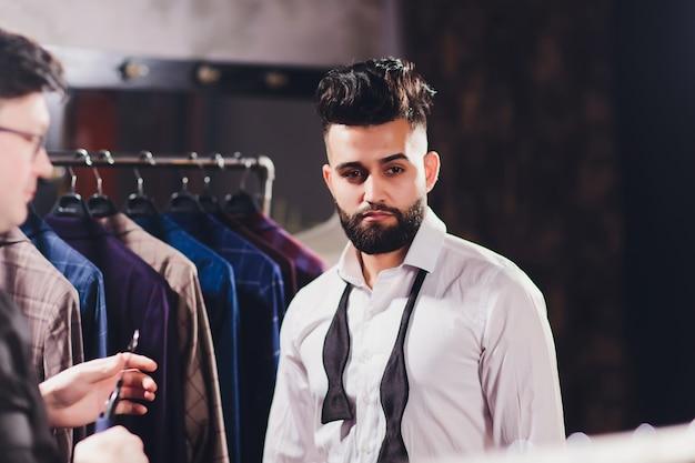Client masculin au centre commercial essayant des vêtements d'affaires aidé par un assistant de magasin
