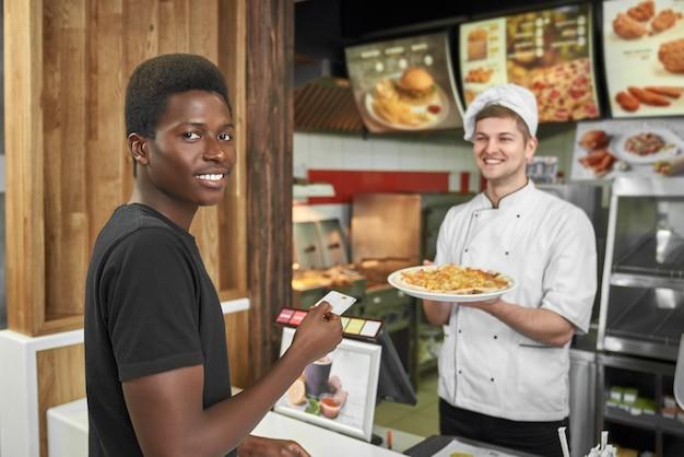 Client masculin regardant la caméra lors de l'achat d'une délicieuse pizza