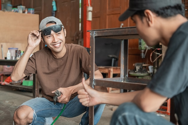 Client masculin satisfait des pouces vers le haut après la commande finie avec le soudeur dans le garage de l'atelier de soudage