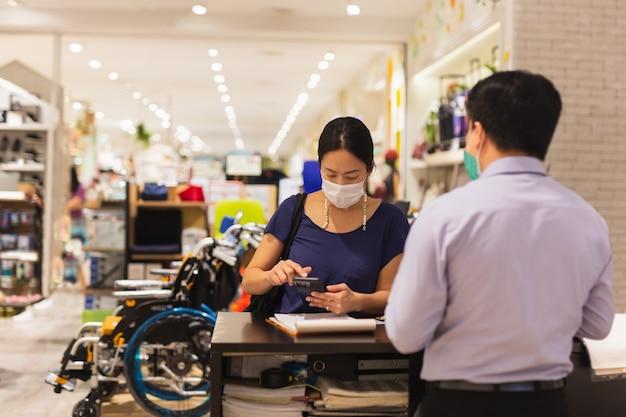Le client en masque de protection effectue le paiement avec un téléphone portable.