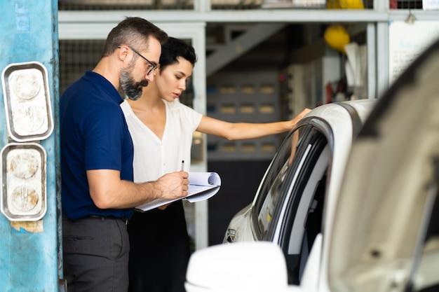 Le client mécanicien et femme vérifie l'état de la voiture avant la livraison. garage de station d'entretien de réparation automobile.