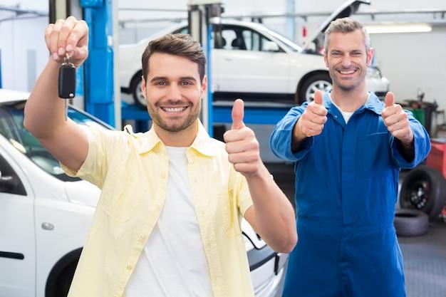 Client et mécanicien souriant à la caméra