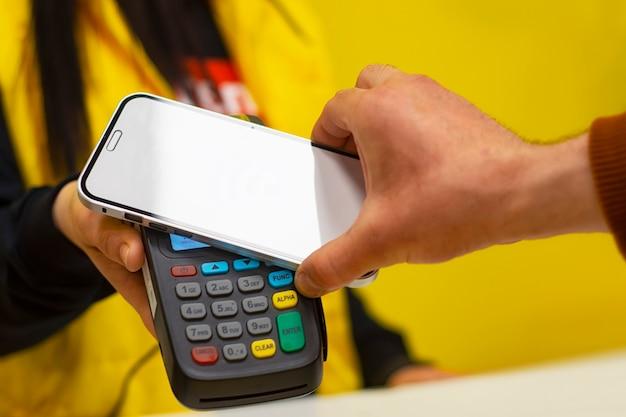 Le client paie avec un smartphone en magasin à l'aide de la technologie nfc. dans le contexte du terminal de paiement et de la fille du vendeur.