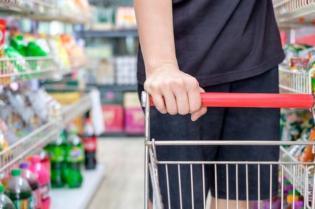 Client avec panier en choisissant un produit dans un supermarché