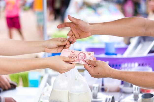 Client payant la facture en espèces au marché en plein air