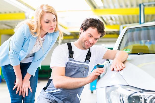 Client et peintre automobile en atelier automobile