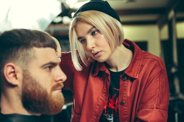 Client pendant le rasage de la barbe dans le salon de coiffure. barbier féminin au salon. égalité des sexes. femme dans la profession masculine.