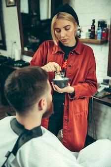 Client pendant le rasage de la barbe dans le salon de coiffure. barbier féminin au salon. égalité des sexes