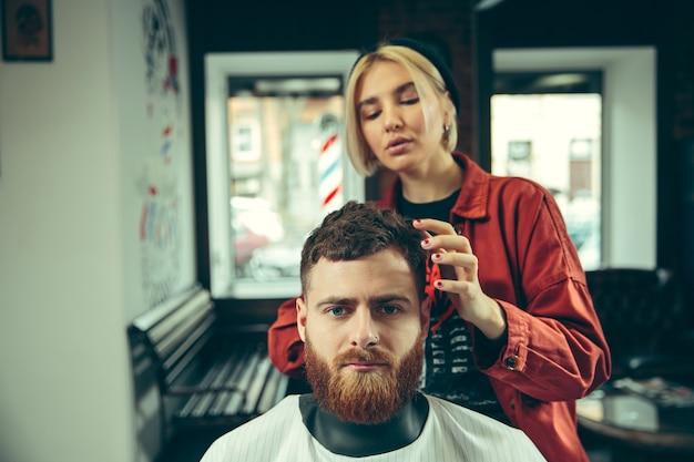 Client pendant le rasage de la barbe dans le salon de coiffure.