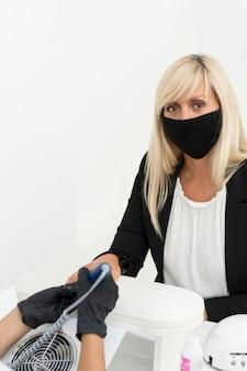 Client portant un masque au salon de manucure