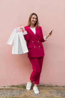 Client portant des vêtements de mode et tenant un smartphone
