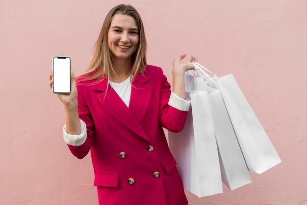 Client portant des vêtements de mode et tenant un téléphone mobile