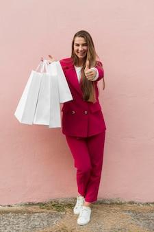 Client portant des vêtements de mode thumbs up long shot