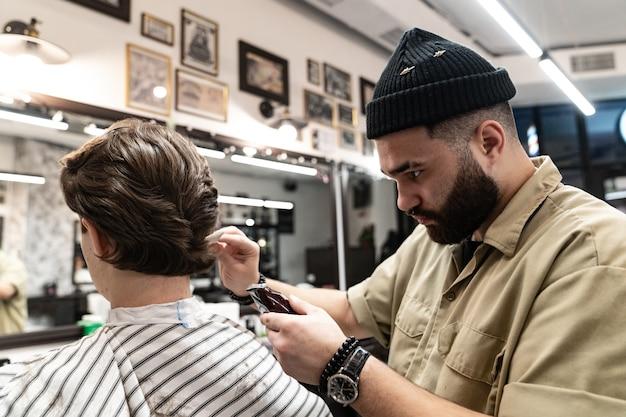 Le client reçoit une coupe et une coiffure dans un salon de beauté. barber sert le client.
