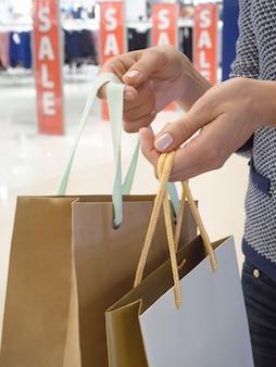Un client avec des sacs à la main dans le magasin