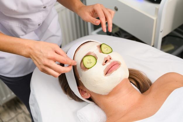 Client de salon de beauté allongé au canapé sous une serviette avec les yeux couverts par des tranches de concombre rondes